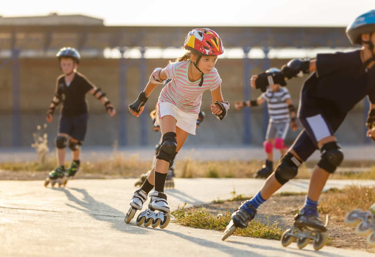 A girl training inline skating with other children