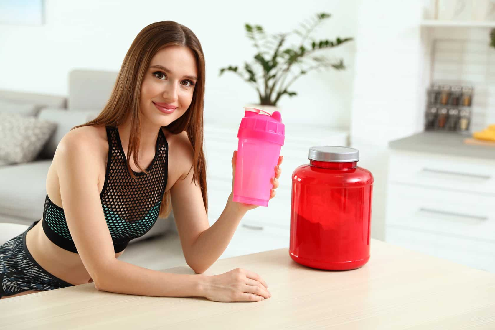 Young woman with bottle of protein shake in kitchen